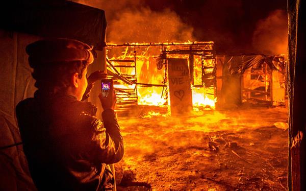 """Un niño refugiado de origen sirio, habitante de la """"Jungla"""" de Calais, fotografía una cabaña ardiendo durante los desalojos policiales."""